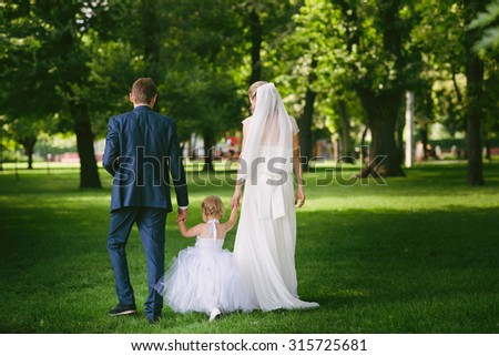 Happy mother and father, the bride and groom with a child playing in the park, parents, family, white dress, attitude, lifestyle