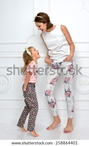 Happy mother and four years old daughter laughing together hugging smiling yelling screaming at each other isolated on a white background - stock photo