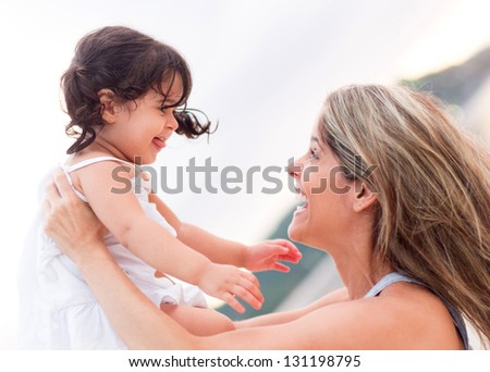 Happy mother and girl having fun outdoors - stock photo