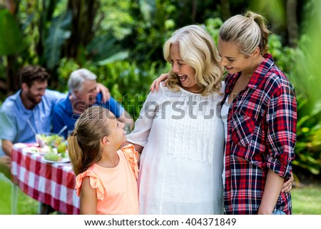Happy mother and granny looking at girl standing in yard - stock photo