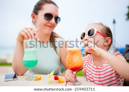 Happy mother and her adorable little daughter at outdoors cafe drinking tropical juice - stock photo