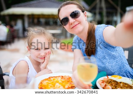 Happy mother and her adorable little daughter at outdoors restaurant taking selfie while having delicious lunch - stock photo