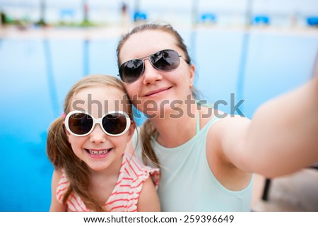 Happy mother and her adorable little daughter outdoors near a swimming pool taking selfie at tropical resort - stock photo