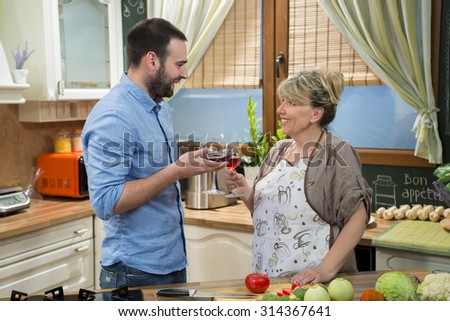 Happy mother and her adult son talking to each other in the kitchen while toasting with red wine and preparing food. - stock photo