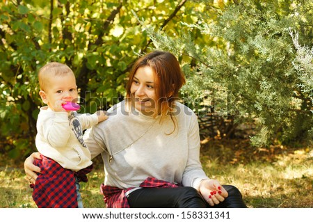 Happy mother and her baby boy is playing in the autumn park - stock photo