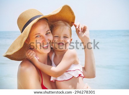 Happy mother and her baby daughter on sea coast. Summer holiday concept - stock photo