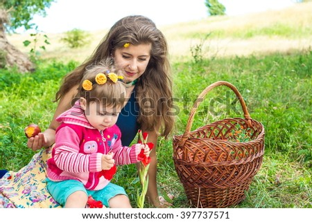 happy mother and her baby walk in the park, young women with kid enjoying sunshine in park. mother and daughter on picnic - stock photo