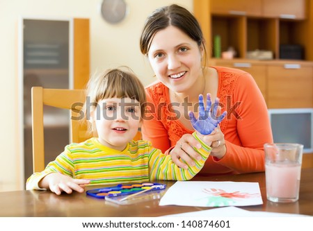 Happy mother and her child painting on paper with handprinting