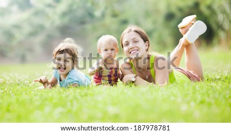 Happy mother and her children  at summer park - stock photo