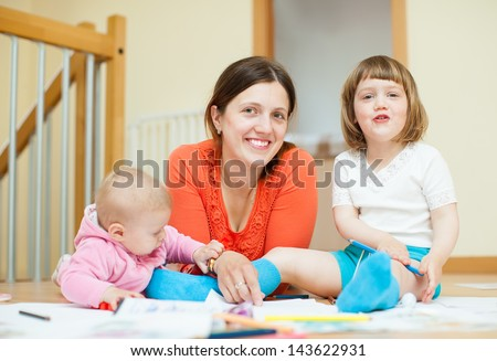 Happy mother and her children drawing on paper at parquet floor