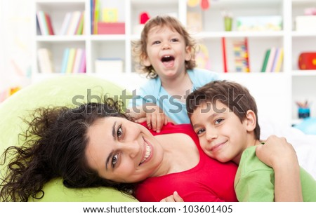 Happy mother and her children playing together at home - motherhood concept