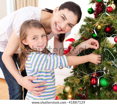 Happy mother and her daughter decorating a Christmas tree - stock photo