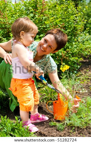 Happy mother and her daughter in the garden - stock photo