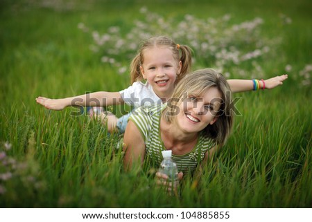 Happy mother and her daughter lying in the grass - stock photo