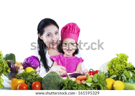 Happy mother and her daughter preparing a salad isolated on white background - stock photo