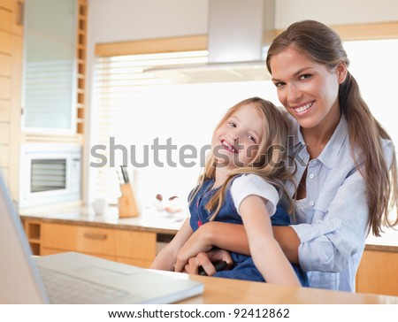 Happy mother and her daughter using a laptop in their kitchen - stock photo