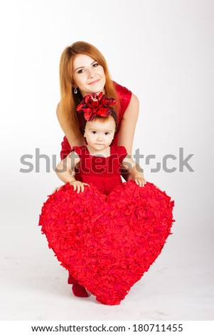 happy mother and her daughter with big red heart - stock photo