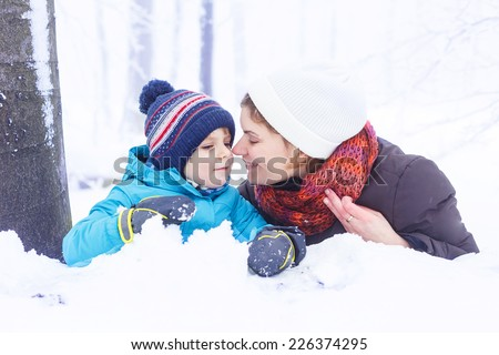 Happy mother and her kid boy having fun with snow in winter forest, hugging and smiling. - stock photo