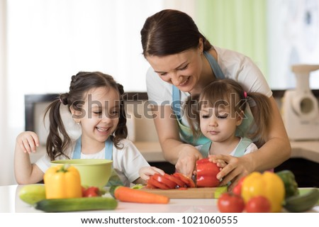 Happy mother and her kids daughters enjoy making healthy meal together at their home