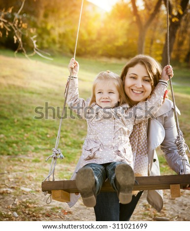 Happy mother and her little baby swing on the background of trees and sky in the autumn park - stock photo