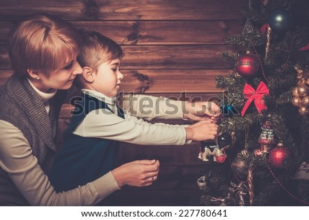 Happy mother and her lIttle boy decorating christmas tree in wooden house interior  - stock photo