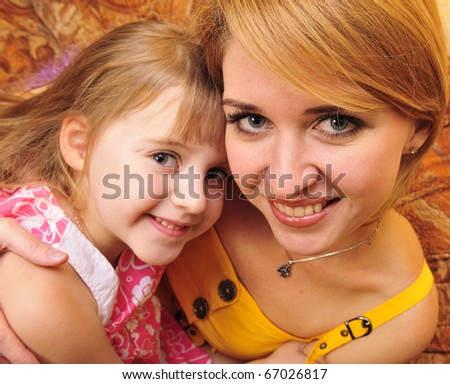 Happy mother and her little daughter at their home - stock photo