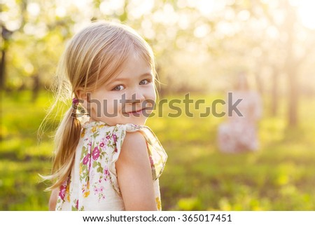 Happy mother and her little daughter in the spring day in a blossoming garden - stock photo