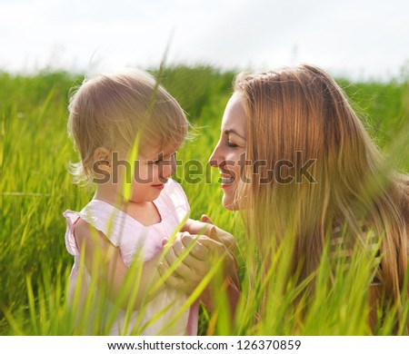 Happy mother and her little daughter in the summer field