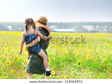 Happy mother and her little daughter in the sunflower field - stock photo