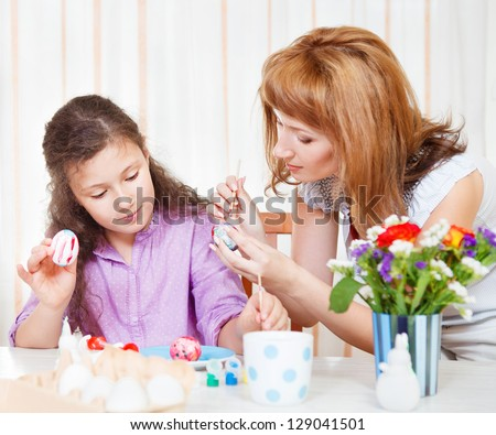 Happy mother and her little daughter painting on Easter eggs