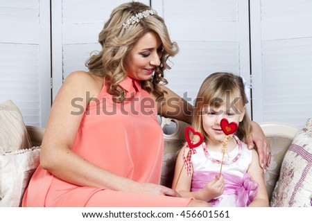 Happy mother and her little daughter with decorative hearts sitting on sofa - stock photo