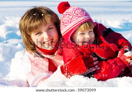 Happy mother and her preschool daughter playing in snow - stock photo