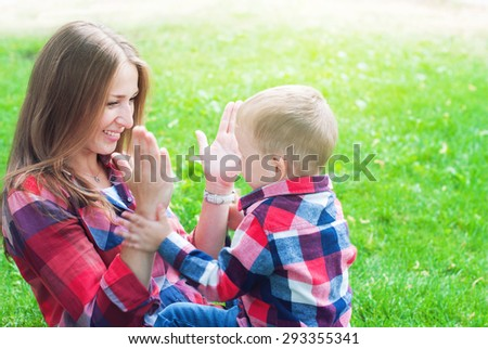Happy Mother and Her Son in Similar Shirts and Jeans Playing in Hands. They are Sitting on Green Grass in the Summer Park - stock photo