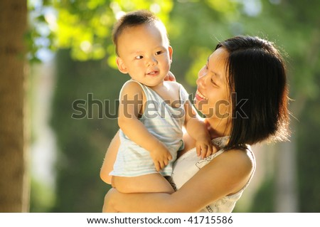 happy mother and her son in the morning sunlight - stock photo