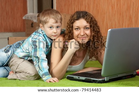Happy mother and her son with laptop  in interior - stock photo