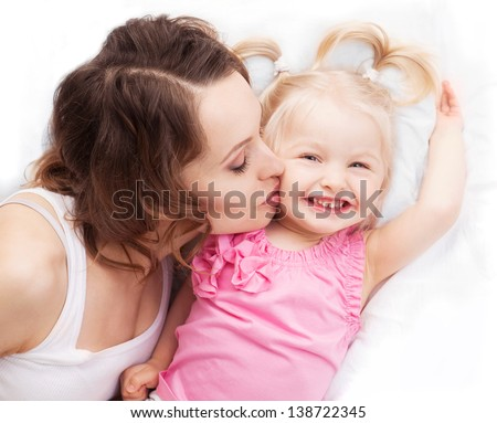 happy mother and her two year old daughter in bed at home, top view - stock photo