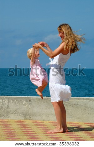 Happy mother and jumping small girl
