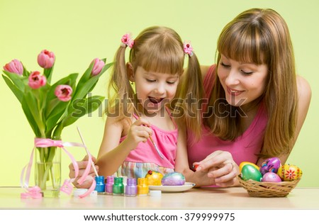 happy mother and kid daughter decorate Easter eggs - stock photo