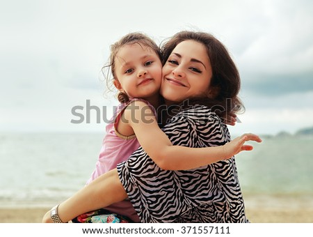 Happy mother and kid girl hugging with natural emotion smiling on blue sea background - stock photo