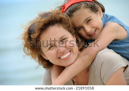 Happy mother and kid on the beach - stock photo