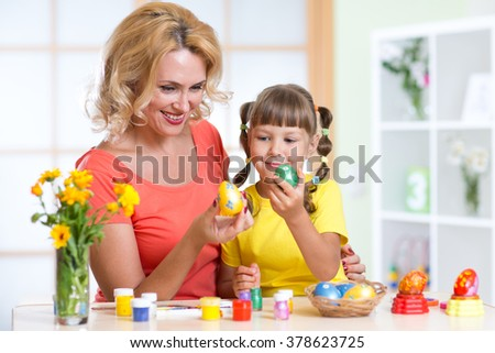 Happy mother and kid painting Easter eggs
