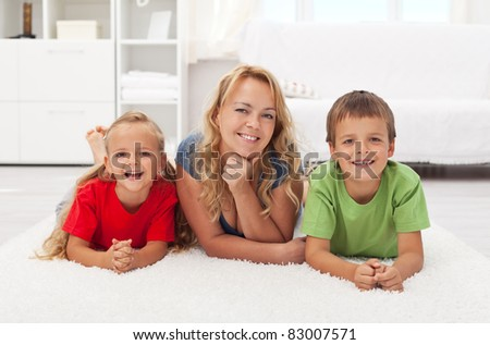 Happy mother and kids at home laying on the floor in colorful casual wear-focus on the woman face - stock photo