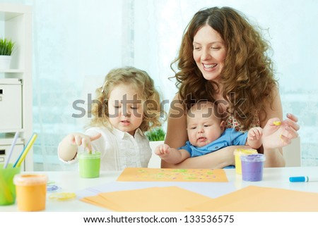 Happy mother and kids doing finger-painting - stock photo