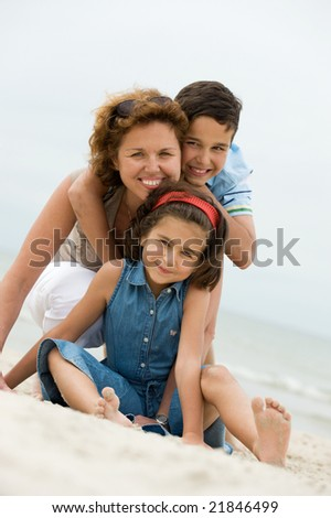 Happy mother and kids on the beach - stock photo