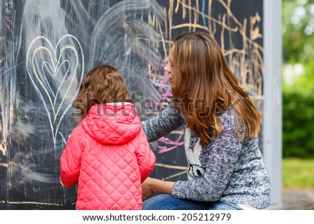 Happy mother and little beautiful daughter drawing with chalk in park, outdoors - stock photo