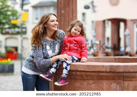 Happy mother and little beautiful daughter having fun together in city - stock photo
