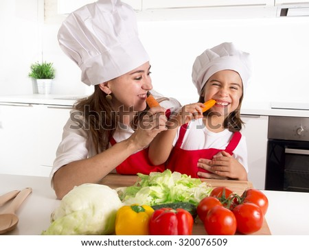 happy mother and little daughter in apron and cook hat preparing salad and eating carrots together having fun at home kitchen smiling playful in healthy vegetable nutrition and education concept - stock photo