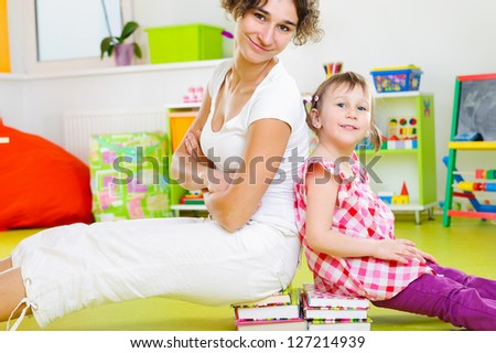 Happy mother and little daughter playing at home - stock photo