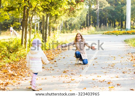 happy mother and  little daughter playing on autumn walk - stock photo