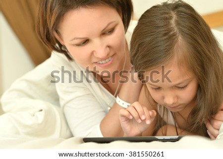 Happy mother  and  little daughter with tablet pc in bed - stock photo